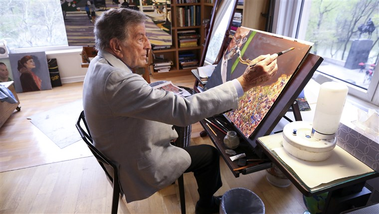 I his New York art studio, Tony Bennett finishes a painting while sitting among several of his completed works.