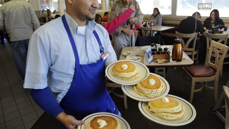 Server Ruben Avalos performs a balancing act with several plates of the free pancakes.