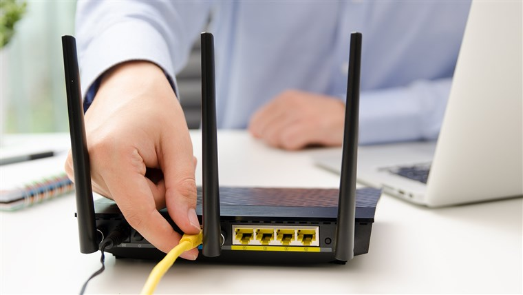 Man plugs Ethernet cable into router