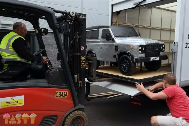 Лара Mason's Land Rover cake gets transported by fork lift.