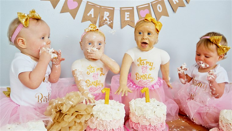 Ан amateur baker has created life-size cake versions of her twin daughters to celebrate their first birthday.